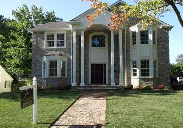 Covered landing with pillars and brick walkway enhance curb appeal