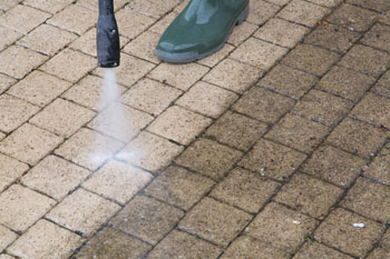 pressure-wash patio bricks and stone